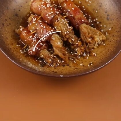 烧烤店里念念不忘的培根金针菇,在家怎么吃?培根卷上金针菇用牙签固定,调好秘制酱汁,放在油锅里小火煎几分钟,一道美味的🍉菜就完成啦!#美食##金针菇培根卷#